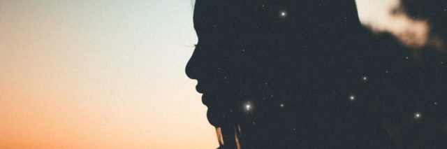 photo of woman backlit by sunset with crescent moon visible and bokeh lights