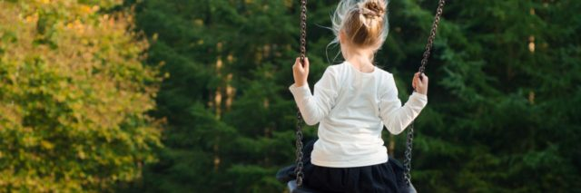 little girl alone on swing near trees