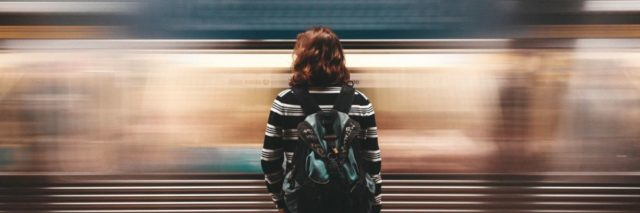 woman standing still in front of moving blurred train
