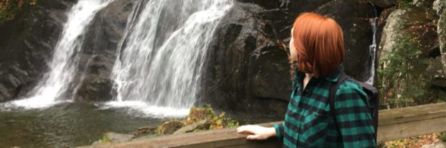 the author standing with her walker by a waterfall