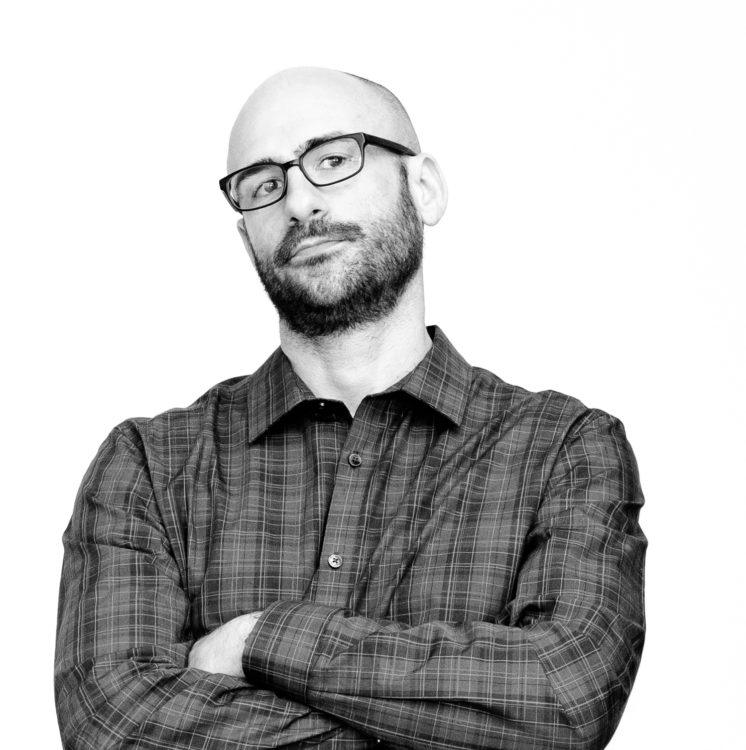 A black and white photo of the author, a white man with a bald head and a beard. He's wearing a plaid buttondown shirt and his arms are crossed.