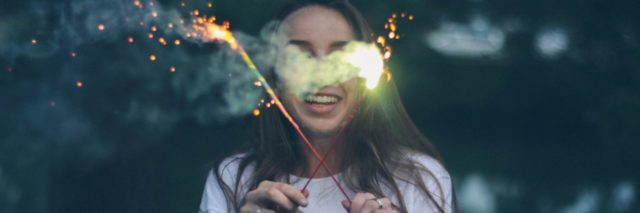 young woman holding sparklers and smiling
