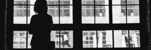 woman silhouetted in front of window in black and white