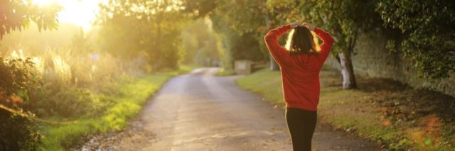 woman in red sweater walking along country road with trees and hedges