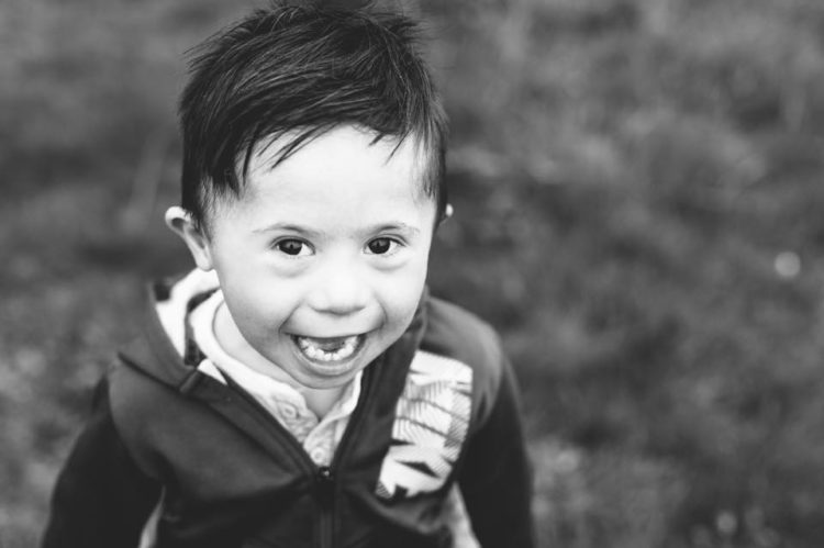 a little boy with Down syndrome smiling