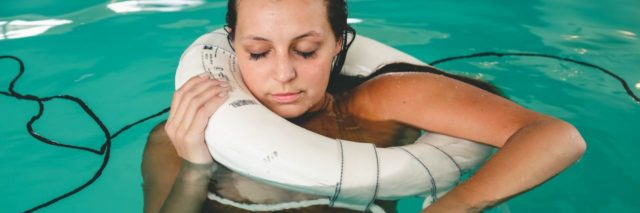 woman holding on to life ring in swimming pool with eyes closed