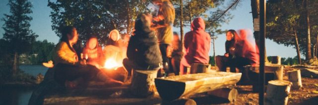 group of young people around campfire at night