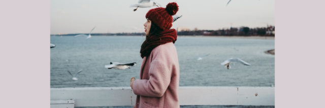 A woman in a winter coat and hat standing by the water. Text reads: 10 Things to Do When You Feel Like You Don't Have Anybody for the Holidays