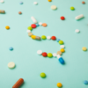 Light blue background with different pills scattered. In the middle, some pills make a dollar sign.
