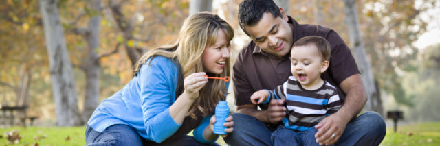 Young family blowing bubbles in a park in autumn.
