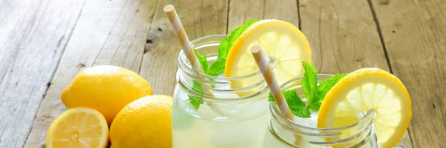 Two mason jar glasses of homemade lemonade on a rustic wooden table.