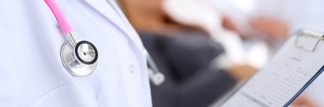 doctor wearing stethoscope and holding clipboard with a patient in the background