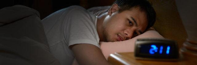 man lying awake in bed staring at alarm clock that reads 2:11 AM