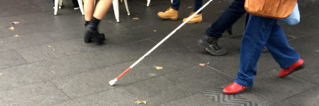 Visually impaired person walking down the street with a cane.