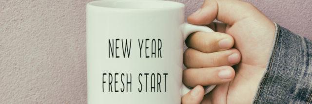 hand holding coffee mug that says new year fresh start