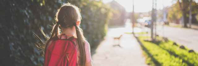 young girl with pigtails and a backpack walking to school