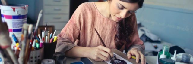 woman designing box or painting on table surrounded by art supplies