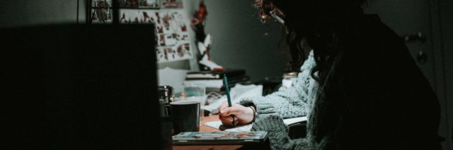 woman hunched over desk drawing or writing