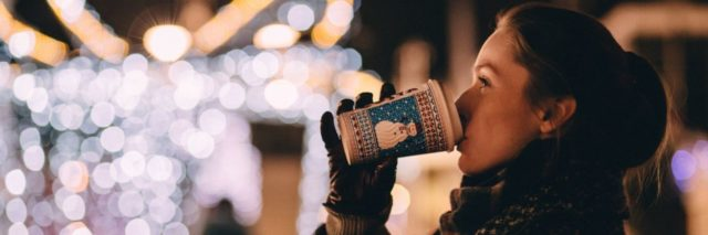 woman bundled up and drinking coffee in front of festive lights