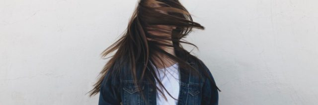 young woman with hair covering her face turning head fast