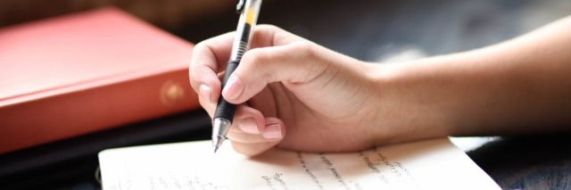 close up of hand holding pen writing in notebook or journal