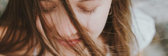 close up of young woman with eyes closed and slight smile