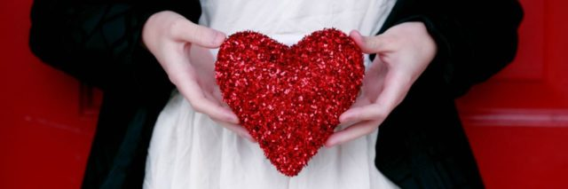 close up of woman holding glitter red heart against white dress