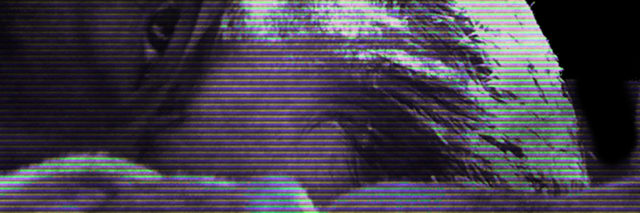 distorted photo of close up of man's face lying in bed looking into camera