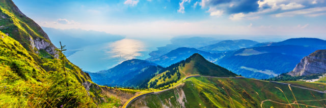 Scenic summer panorama from Rochers de Naye mountain peak with green grassy hills, flower meadows and Geneva Lake in Alps, Switzerland.