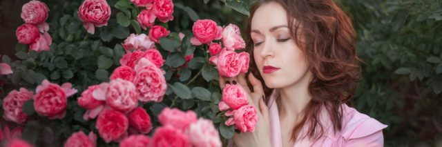 photo of woman standing beside pink roses with eyes closed and hands raised to flowers
