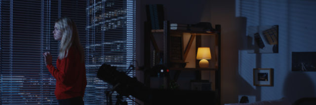 Medium wide shot of a lonely woman looking out a window at night then walking away