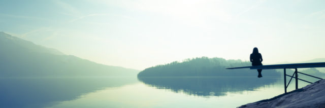 Woman sitting alone on the shore of the lake.
