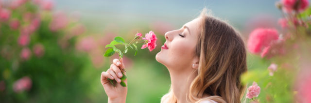 Woman stopping to small the roses.