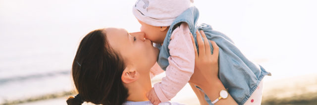 a mom is holding her baby and kissing her on the cheek at the beach
