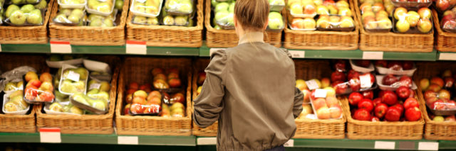 A woman is buying produce at the grocery store.