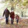 two grandparents hand in hand with their grandson walking in a park