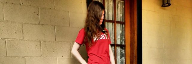 Jess standing with a cane, wearing her Mighty t-shirt.