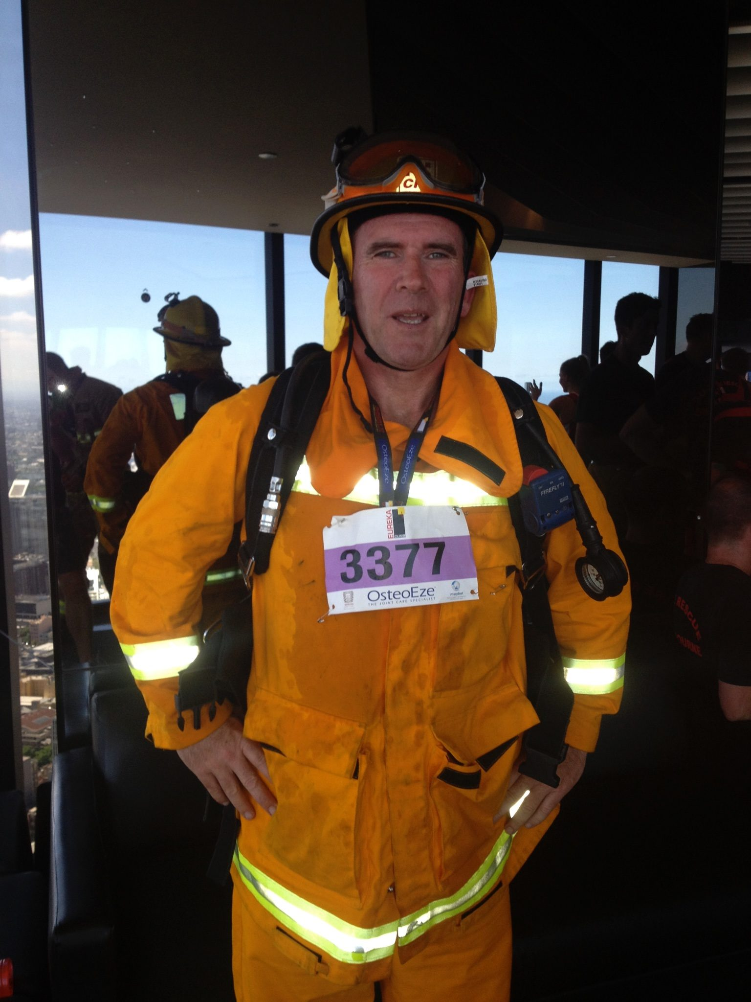 photo showing 50-year-old man in volunteer firefighter uniform with charity number on his chest looking tired