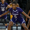 Jordan Hankins in her purple Northwestern basketball gear on the court. Her arms are spread out anticipating her next move in the game.