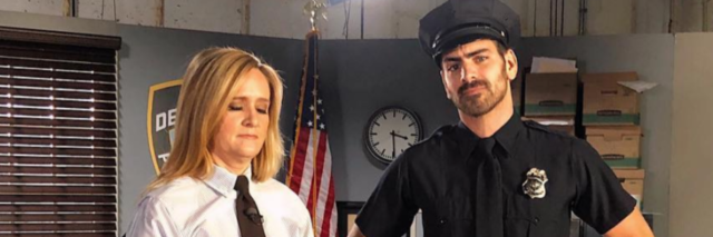 Samantha Bee in a white shirt and tie with Nyle DiMarco in a police uniform.