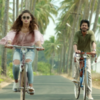 still image of bollywood movie Dear Zindagi showing male and female actors riding down tree-lined road on bicycles