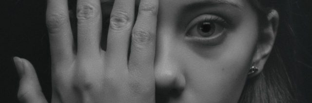 black and white photo of young woman covering one eye with hand and looking into camera
