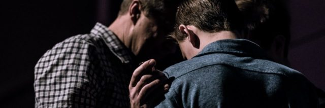 two men in semi darkness with one man's hand on the other's shoulder in support or prayer