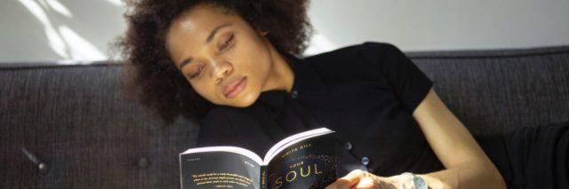woman lying on sofa reading book in sunlight