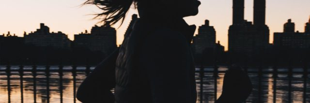photo of woman silhouetted against sunset and new york skyline running along river