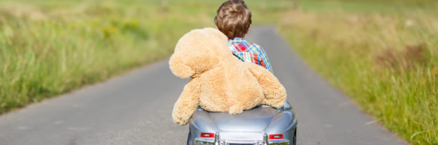 Little boy driving a toy car with a stuffed teddy bear in it