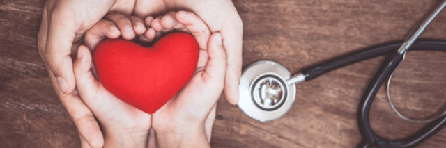woman and child's hands holding a heart, with a stethoscope next to their hands