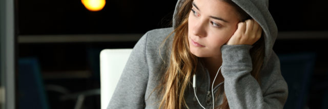 photo of young woman wearing hooded sweater with earphones and phone