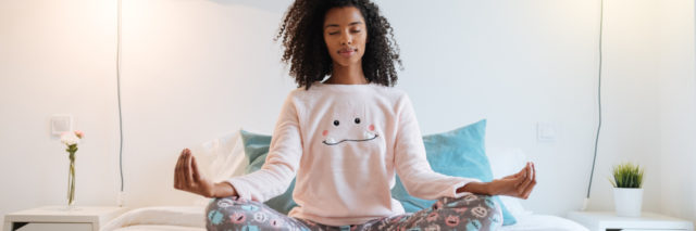 young woman sitting on bed meditating or practicing yoga