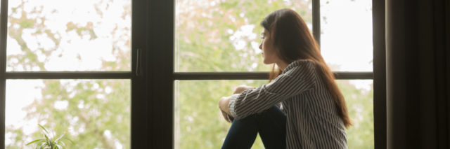 A girl is sitting in a room thinking and looking out of the window.